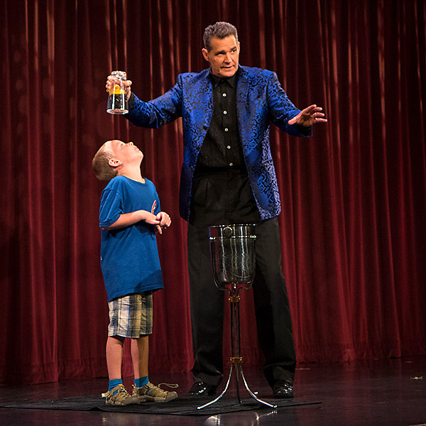 [Photo: A volunteer from the audience looks nervously up at a glass of water, suspended upside down over his head by the magician Rick Wilcox.]