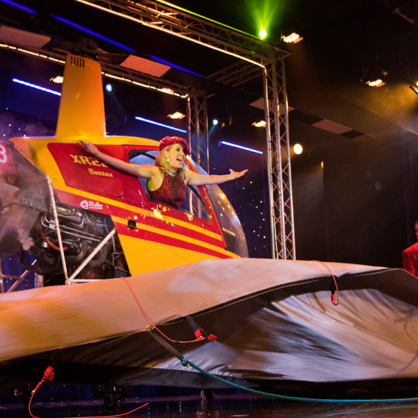[Photo: Suzan Wilcox poses in a helicopter on the stage of the Rick Wilcox Magic Theater.]